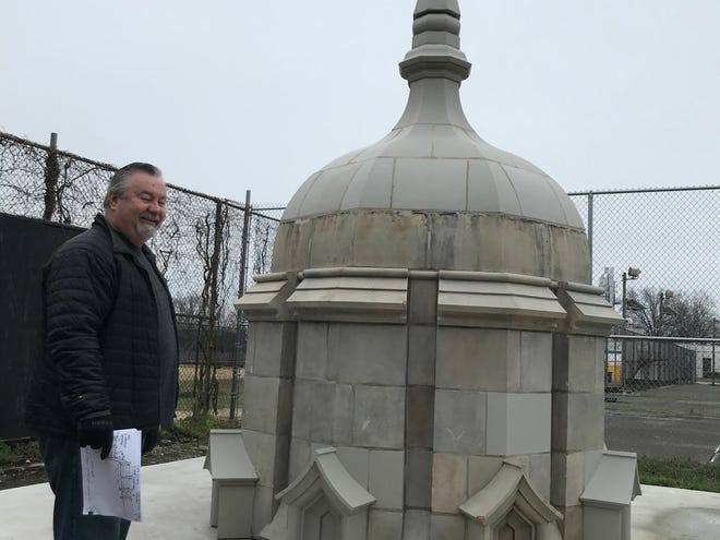 Jack O'Byrne of the Camden County Historical Society stands near one of the spires that used to be atop Camden High School. The spire will be a feature of a new outdoor sculpture and rain garden at the Park Boulevard site.