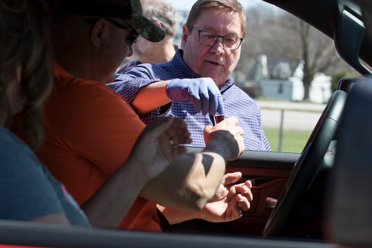 Bob Banks gives parishioners juice for their drive-thru communion at Real Joy Community Fellowship Church.