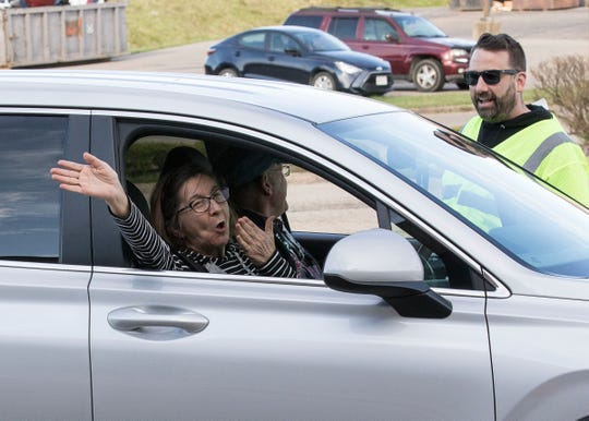 Patty Wallingford blows air kisses to thank Centerpoint Church and Jimmy John's for the free sack meals. Each car was able to get up to six bags for a family on March 30, 2020.