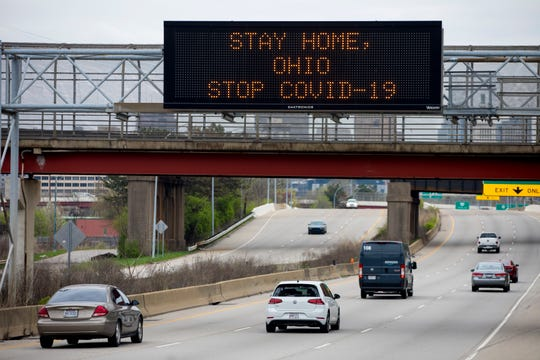 Cars drive under a sign asking for people to stay home to prevent the spread of the new coronavirus on Highway 50 near downtown Cincinnati on Tuesday, March 31, 2020.