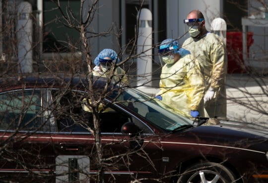 Jewish Hospital health care workers work their drive-thru testing site in Sycamore Township along Kenwood Rd, Monday, March 30, 2020. The new coronavirus pandemic has caused outdoor testing sites in our area hospitals.
