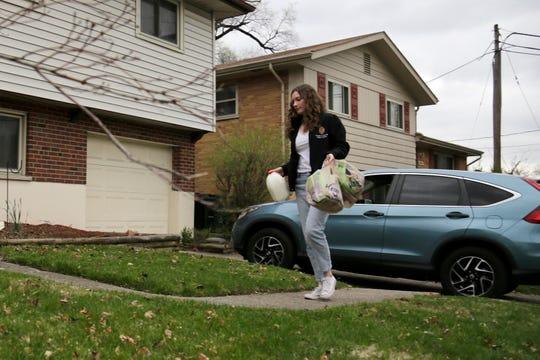 Alyssa Kelder, 24, a medschool student at the University of Cincinnati, delivers groceries to the home of Yvonne Carrell, 67, in the Finneytown neighborhood of Cincinnati on Tuesday, March 31, 2020. Kedler, and a group of fellow UC medical school students, have started delivering groceries and running errands for higher-risk people, and those in need, as they shelter from the ongoing COVID-19 pandemic.