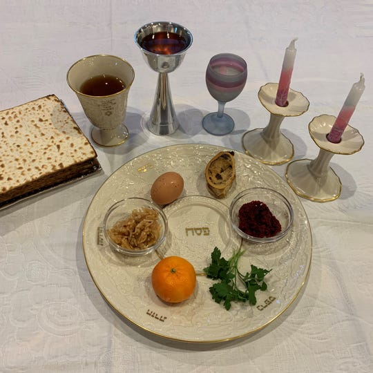 A Passover Seder plate surrounded by matzo, Kiddush cups and candles.