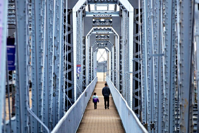 Lance Montanez and his daughter, Willow, 4, of Fort Mitchell, walk across the Purple People Bridge from Newport, Ky., to Cincinnati on Tuesday, March 31, 2020.