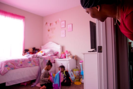 Kenia Ayala peers into the bedroom of her daughter Makhaya, 5, where she and her brother Malakai, 2, pack backpacks full of toys before venturing out to the yard at the Ayala household in Clarksville, Tenn., on Tuesday, March 31, 2020.