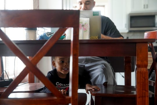 Malakai Alaya, 2, peers out from under the table his dad Jose Ayala, background, is using as a temporary desk while working from home at the Ayala household in Clarksville, Tenn., on Tuesday, March 31, 2020.