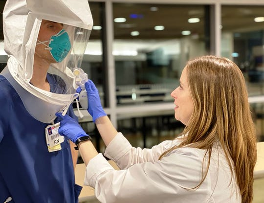 A nurse at Robert Wood Johnson University Hospital New Brunswick helps a colleague secure their personal protection equipment while battling COVID-19.