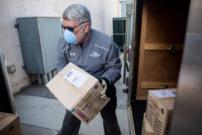 Terry Evans of Patterson Dental Supply unloads boxes of personal protective equipment to be donated to the Polk County Health Department on March 31 in Des Moines, Iowa.