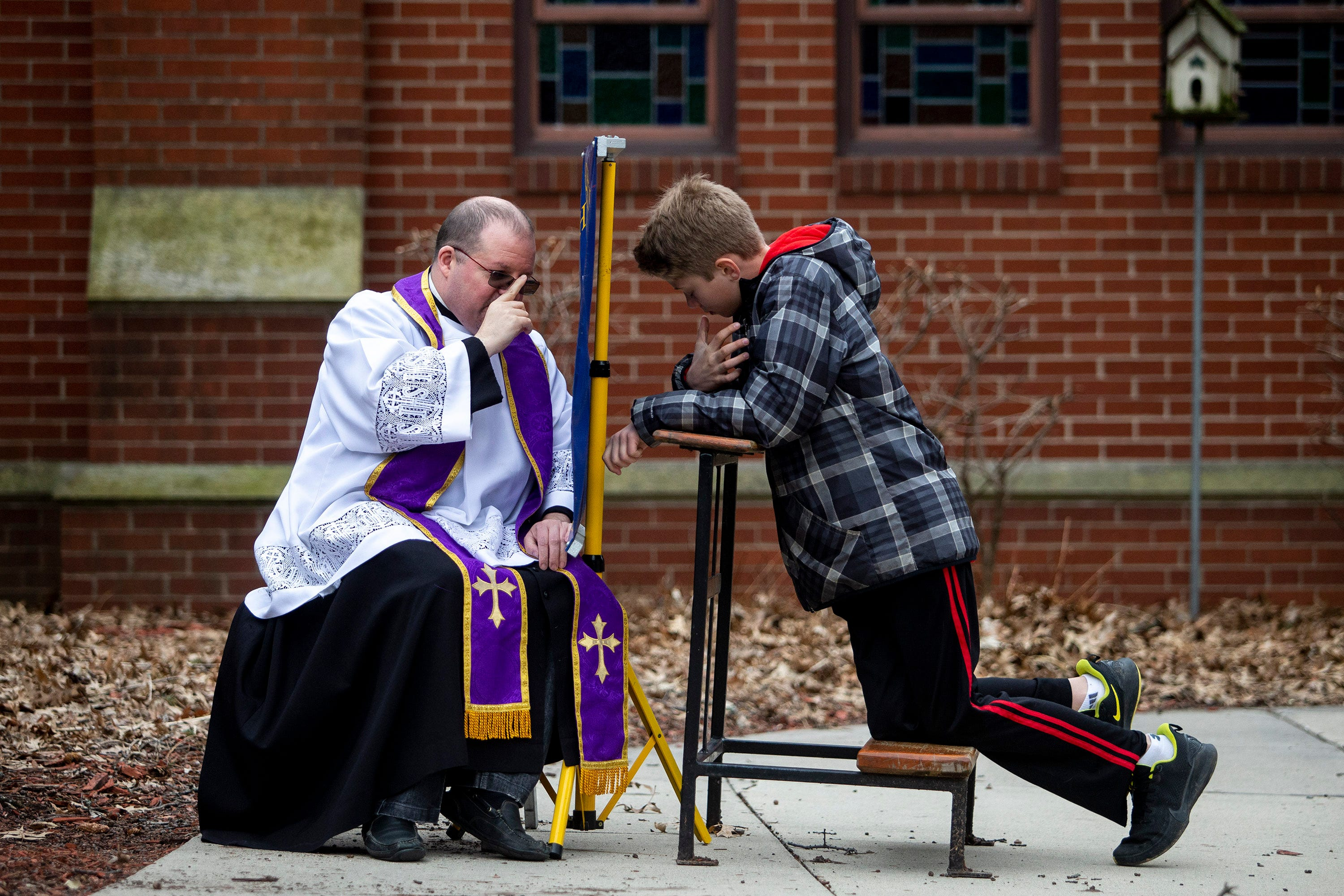 The Rev. P.J. McManus, of Christ the King Church, gives a blessing while hearing confession from Johnny, a parishioner of Christ the King, outside of the church's entrance on Tuesday, March 24, 2020, in Des Moines. McManus moved confession outside after the rise of COVID-19 in Iowa.