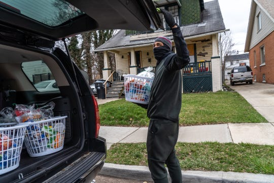 G.O.D.S. Plan founder Mike Rogers of Detroit carries a quarantine basket of essential items to deliver to a community member's home in Detroit on March 30, 2020.