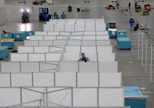 Workers start to assemble the framing and partitions for individual rooms as part of the alternate care facility inside Hall C of the TCF Center in Detroit, Michigan on March 31, 2020.