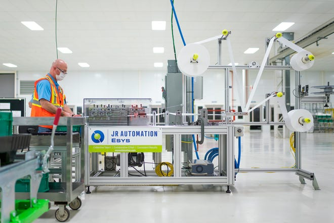 Aaron Leitz sets-up and tests a machine that will be used to manufacture Level 1 face masks Sunday, March 29, 2020 at the General Motors Warren, Michigan manufacturing facility. Production will begin next week and within two weeks ramp up to 50,000 masks per day, with the potential to increase to 100,000 per day. (Photo by John F. Martin for General Motors)