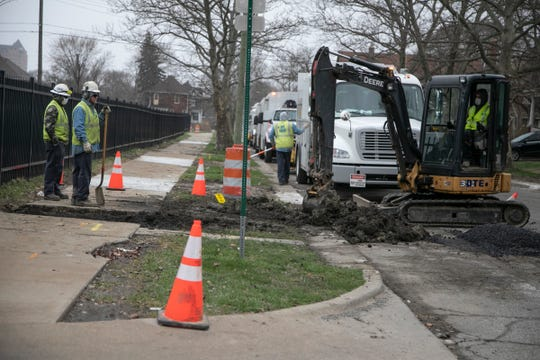 DTE workers fix a gas line on March 31, 2020, on Lothrop Street on Detroit's westside. Utility workers continue to work during the Novel Coronavirus outbreak.