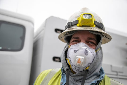DTE fitter Derik Minutolo smiles through his N95 mask on March 31, 2020, as he and co-workers repair a gas line on Lothrop on Detroit's westside. Utility workers continue to work through the Novel Coronavirus outbreak.