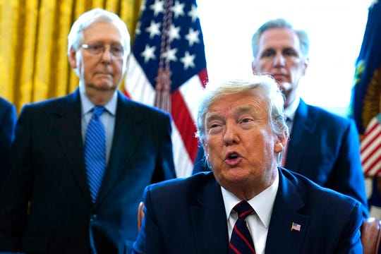 President Donald Trump speaks before he signs the coronavirus stimulus relief package in the Oval Office at the White House, Friday, March 27, 2020, in Washington, as Senate Majority Leader Mitch McConnell, R-Ky., and House Minority Leader Kevin McCarthy of Calif., listen.