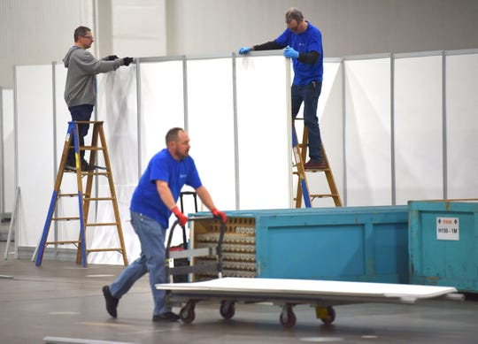 GEMS Detroit Local 687 carpenters, including, Paul Grode, right, of Northville, install stabilizers on top of cubicles that help hold walls in place as they build a temporary hospital at TCF Center.
