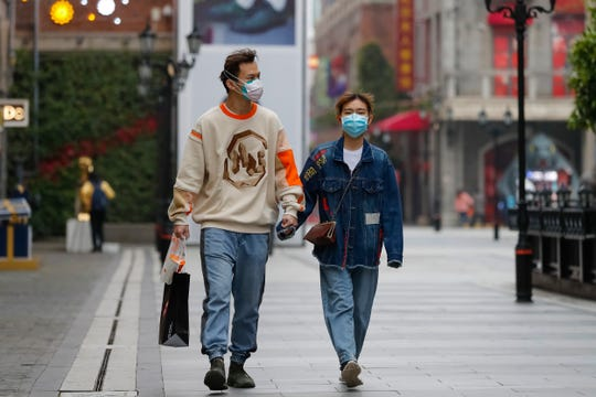 A couple wearing protective masks to prevent the new coronavirus outbreak walk on a re-opened commercial street in Wuhan in central China's Hubei province on Monday, March 30, 2020.