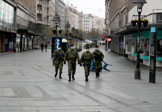 Serbian army soldiers patrol in Belgrade's main pedestrian street, in Serbia. In the ex-communist Europe and elsewhere, rulers are assuming more power while they introduce harsh measures they say are necessary to halt coronavirus spread.