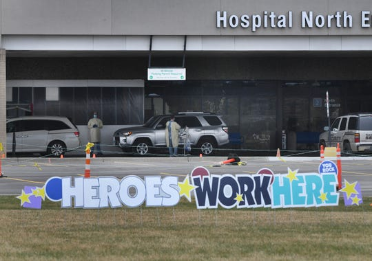 'Heroes Work Here' signage on the front lawn of Beaumont hospital, with coronavirus testing in the background, at the North entrance in Royal Oak, Michigan on March 31, 2020.