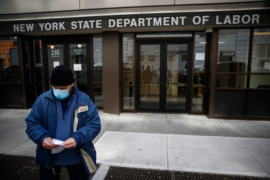 In this March 18, 2020 file photo, visitors to the Department of Labor are turned away at the door by personnel due to closures over coronavirus concerns.