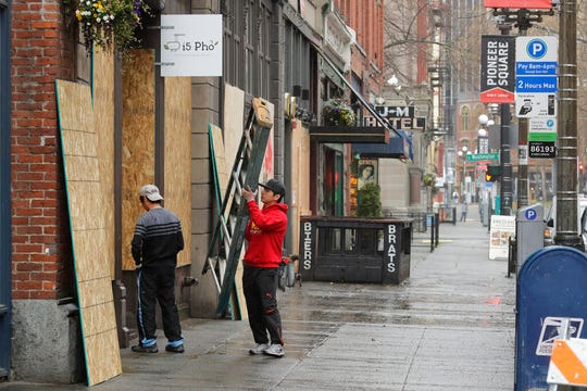 hu Dang, right, the owner of i5 Pho restaurant, boards up his business, Monday in Seattle's downtown Pioneer Square neighborhood.