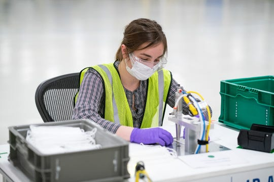 Engineers and technicians set-up and test the machines that will be used to manufacture Level 1 face masks March 30, 2020 at the General Motors Warren manufacturing facility.