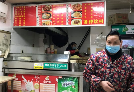 """Owners of a store selling a local favorite """"reganmian,"""" or """"hot dry noodles,"""" prepare takeaway orders in Wuhan in central China's Hubei province, Tuesday, March 31, 2020."""