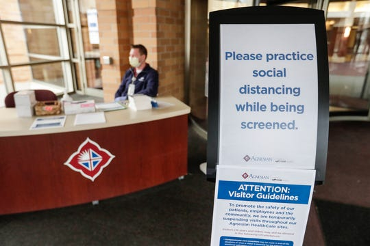 A sign greets everyone entering St. Agnes Hospital on March 26 in Fond du Lac as Steve Smith waits to screen all employees, visitors and patients entering the hospital for a fever, and asks them questions pertaining to symptoms of the coronavirus.