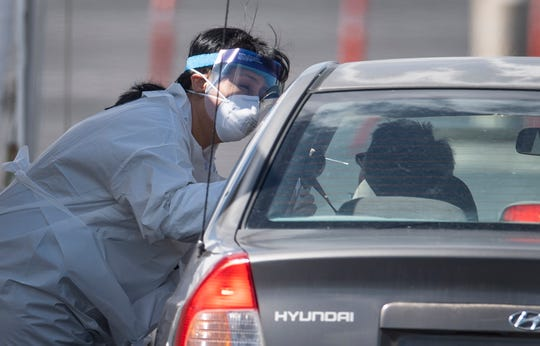 An employee from the Weld County (Colo.) Department of Public Health and Environment tests a man for the novel coronavirus at a drive-thru testing station in Loveland, Colo. on Monday.