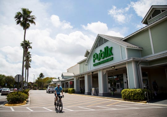 A cyclist rides through the Colonial Crossing Shopping Center in Fort Myers on Tuesday, March 31, 2020, in Fort Myers.