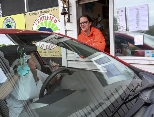 Misty Shular of Williamston gets a drive up order from Missy Taylor at the store at Happy Cow Creamery in Pelzer Tuesday.