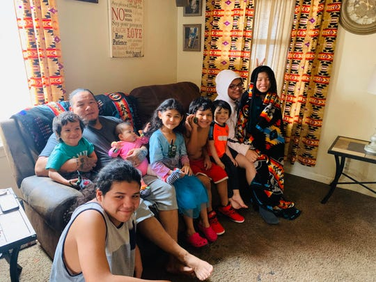 The Stanfield LaForge family sits on a couch together. During the coronavirus pandemic, the Stanfield LaForge family has had nine children and two parents living in a four-bedroom home.