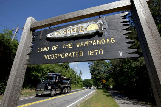 """In this June 25, 2018, photo, a wooden sign advises motorists of the location of Mashpee Wampanoag Tribal lands in Massachusetts. Tribe Chairman Cedric Cromwell announced in a post on the tribe's website on Friday, March 27, 2020, that the federal Bureau of Indian Affairs told them that the tribe's reservation will be """"disestablished"""" and its land taken out of trust, per an order from Secretary of the Interior David Bernhardt."""