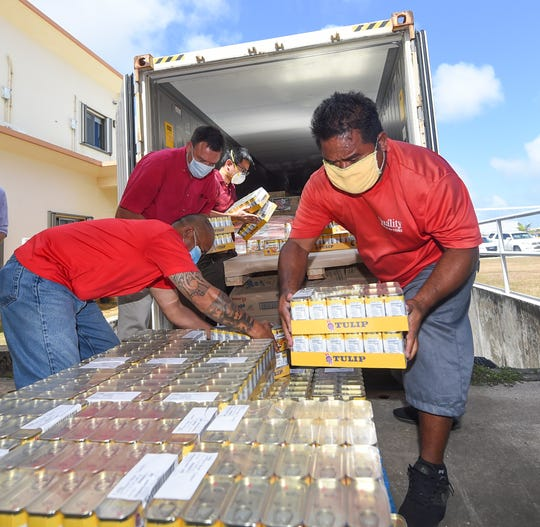 Quality Distributors employees offload pallets of food and drink products during a donation delivery at The Salvation Army Guam Corps Tiyan headquarters on March 31, 2020.