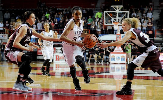 Henderson County's DeAsia Outlaw (center) drives past Ashland's Shelby Gransberry (left) and Alexis Robinson during the 2015 state tournament in Bowling Green.