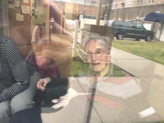 Alda Haravon, 91, looks at her daughter Lea Haravon Collins through a window from Oaknoll Retirement Residence, March 19, 2020, in Iowa City. Visitors have not been allowed at the center due to the COVID-19 pandemic since March 9.