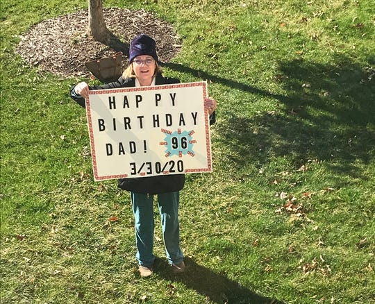 Anne Wallace holds up a sign for her father Norm Kallaus, 96, as he looks out from his window while they celebrate his birthday, Monday, March 30, 2020, at Oaknoll Retirement Residence in Iowa City, Iowa.