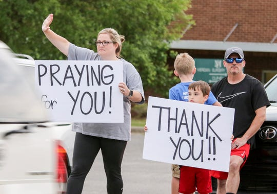 Robien Gressett y su hijo Briggs portan letreros con mensajes de apoyo a personal médico.