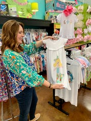 Mary Ann Wachtel shows a dress available at Leap FrogConsignment & More. Because of the spread of coronavirus, the store is closed to customers but has curbside pickup and also ships orders that are the result of customers shopping via social media.