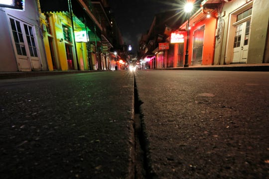 A view during the coronavirus outbreak of the nearly deserted scene on Bourbon Street, which is normally bustling with tourists and revelers, in the French Quarter of New Orleans. (AP Photo/Gerald Herbert)