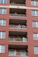 Residents of the Lambeth House, where a cluster of the coronavirus has formed, react from balconies as opera singers Irini Hymel and Bryan Hymel sing to the quarantined residents in New Orleans, Friday, March 20, 2020. (AP Photo/Gerald Herbert)