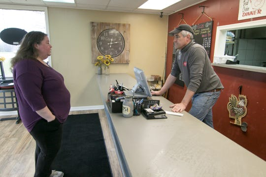 Mary's Fabulous Chicken and Fish customer Lee Robertson of Howell puts in her order to owner Dennis Hellweg Tuesday, March 31, 2020. Mary's has been able to stay open during the COVID-19 crisis, although many other restaurants have closed or reduced their hours.