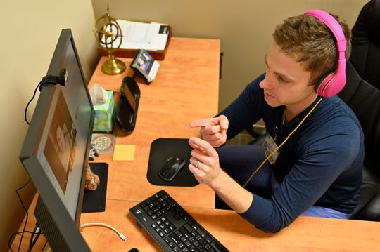 Dr. Brian Plato, a neurologist with Norton Healthcare, meets with a patient through a telehealth visit in his office.