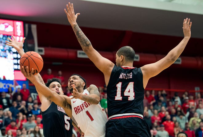 Redford Carlik Jones (1) drives to basket between Gardner Webb defenders Jose Perez (5) and Brandon Miller (14) during the first half of the Big South conference NCAA basketball championship game in Radford, Va., Sunday, March 10, 2019.