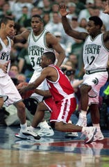 Travon Davis of Wisconsin moves to pass the ball as he is guarded by Andre Hutson (34) and Mateen Cleaves (12) of Michigan State during the NCAA Men's Finals Four Game at the RCA Dome in Indianapolis, Indiana, on April 1, 2000.