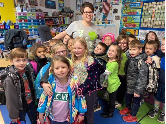 Ontario kindergarten teacher Julie Shreffler is shown with her students in a group hug in March before they left Stingel Elementary School due to the coronavirus pandemic.