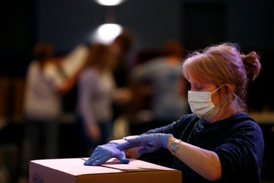 Jamie Rutherford wears a protective mask and gloves as she works with fellow volunteers at CrossPoint Church where they are putting together food packages to feed a family of four for a full week, during one of two weekly distributions, from three separate DeSoto County church sites, on Monday, March 30, 2020.
