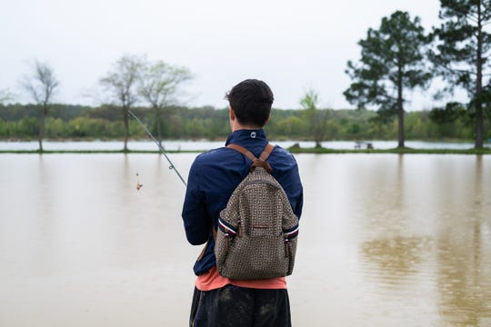 Colby Reed, 18, fishes in the rain at Catchem' Lake, Monday, Mar. 30, 2020, in Memphis, TN.