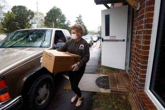 Beth Gregory helps to distribute food packages at CrossPointe Church that will feed a family of four for a full week, during one of two weekly distributions, from three separate DeSoto County church sites, on Monday, March 30, 2020.
