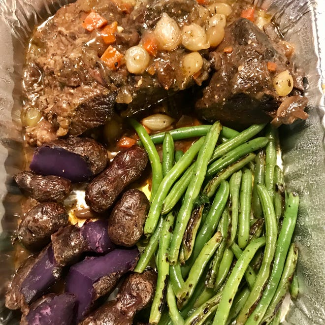 One of the entrees for takeout at Tess, 2499 N. Bartlett Ave., is short rib for one, two or four, in demi-glace with pearl onions, green beans and purple fingerling potatoes.
